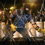 A riot police officer installs barbed wire as others block the street towards the Presidential Residence to prevent a march of anti-government protesters, supporters of the armed group who have been holed inside a police station, in Yerevan, Armenia, Saturday, July 30, 2016. Armed members of an opposition group barricaded inside a police station in Armenia's capital shot an officer dead on Saturday, police said. (Hrant Khachatryan/PAN Photo via AP)